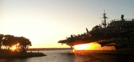 The glow of sunset reflects off the hull of the USS Midway.