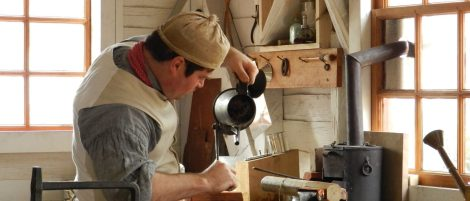 A tinsmith's apprentice at a one of Williamsburg's recreated workshops.