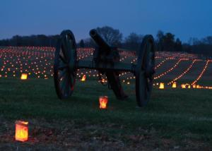 A cannon and a field of luminaria at Antietam during the Memorial Illumination.