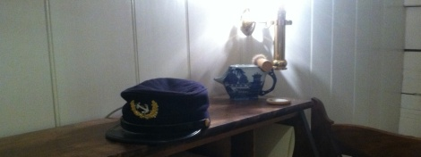 A cap and shaving mug atop the desk in the executive officer's quarters on the USS Constellation.