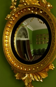 Homewood's reception hall is reflected in a gilded convex mirror.