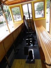 The levers and brakes are in the center of the cable car, between the outward-facing seats.