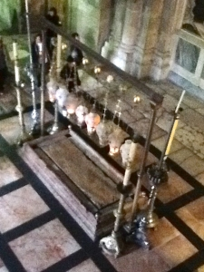 Lanterns and candles surround the marble slab outside the tomb in the Church of the Holy Sepulchre.