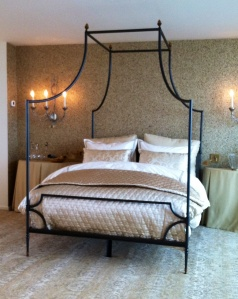 The master bedroom is almost traditional but the bed frame and the unusual wall treatment push the envelope.