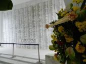 The names of the sailors have been inscribed in the wall of the memorial. Visitors leave flowers and leis in tribune.