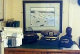 Captains' lids. Behind them is a photo of liberty ships in convoy.