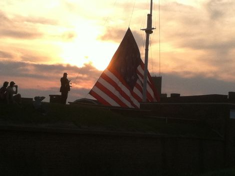 The large flat is lowered at sunset. A small storm flag flies at night.