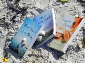 Three books by Christine Lemmon among the sands and shells of Sanibel.