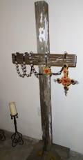 Inside the old church, a rustic cross has been decorated with a colorful rosary.