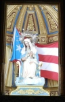 A flag of Puerto Rico is draped behind a statue of Mary and Jesus in the Cathedral of San Juan Bautisto.