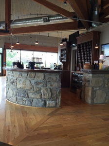 A curvaceous stone bar dominates the tasting room .