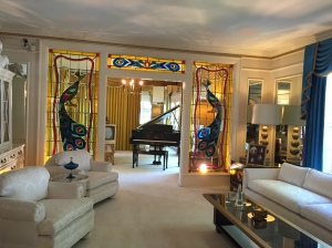 Peacock stained glass separates Elvis piano from his living room.