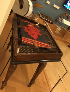 This cimbalom is accompanied by its colorful dust cloth, its hammers and the tuner.