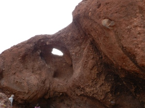 Erosion has caused reddish sandstone to be eroded away, forming caves and even holes.